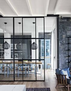 Large-glass-divider-with-black-frame_Pendant-lamp_Brown-long-table_Blue-chair_Matural-stone-wall_Wooden-floor_White-painted-ceiling